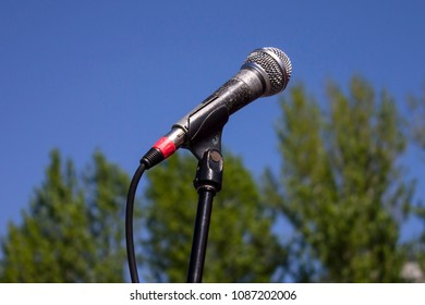 Black old microphone, mic, standing outdoors on the open air with ,lue sky and green trees background