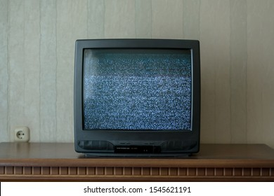 black old TV with static on screen standing on wooden table in room of home