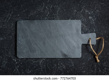 Black old-fashioned stone and slate cutting board on black background. Place for text. Top view