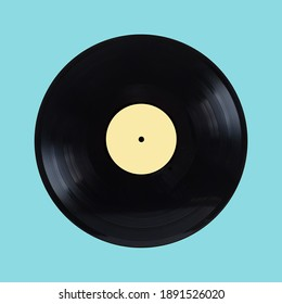 Black oldschool long-play vinyl record with yellow label isolated on cyan background front view closeup