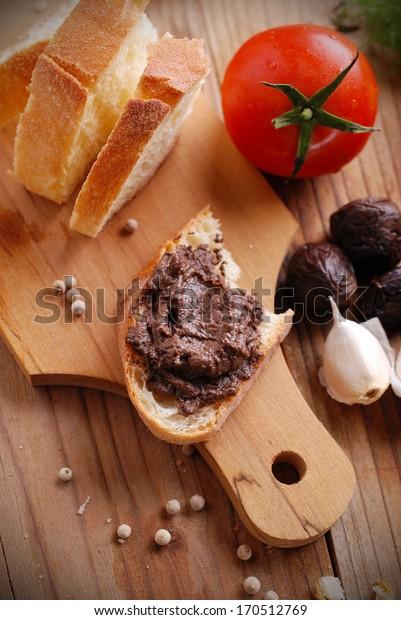 black olive pate spread on slice of bread