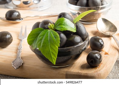 Black olives in glass cups decorated with green leaves on a wooden tray and vintage crockery with shallow depth of focus