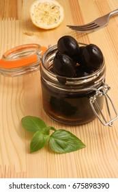 Black olives in a glass jar, basil and fork
