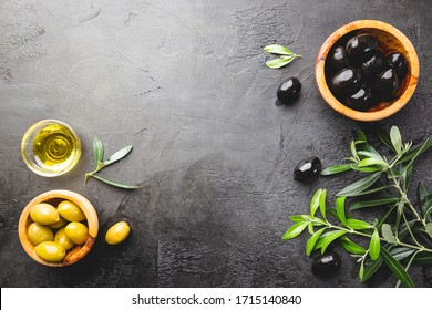 Black olives and olive oil in wooden bowls on black background. Top view with copy space for text.
