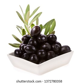 black olives are sitting in a white ceramic bowl decorated with green olive leaves isolated on white background