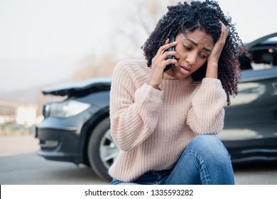 Black oman making a phone call after having a car crash