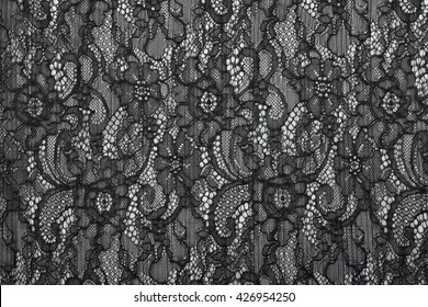 Black openwork lace background texture. Black guipure. Black fabric with ornament. Background from black lace with pattern with form flower