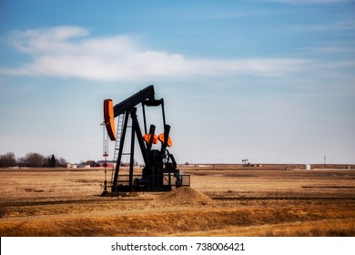 A black and orange oil rig pumpjack in a rural countryside landscape