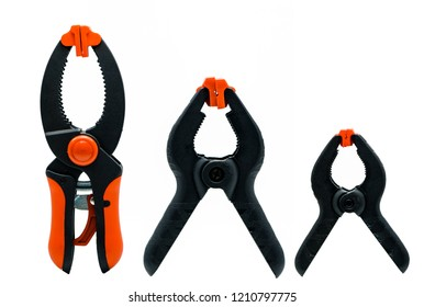 Black and orange spring clamp isolated on white background. Set of small, medium, and big size of plastic clamp. Clamping tools for carpentry work. Hand tools for handicraft. Clamping equipment.