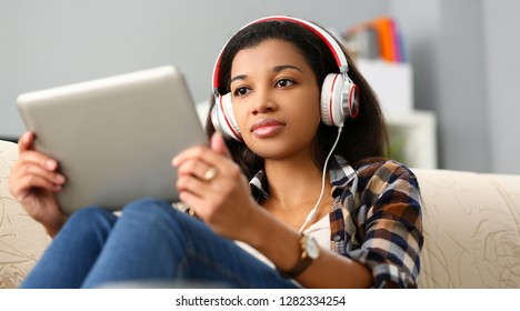Black ordinary female american teen portrait at home sofa remote education concept. Girl hold tablet in hand music apps teacher checks homework online university library learning foreign languages