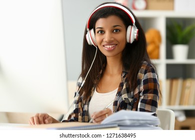 Black ordinary female designer workplace portrait at home remote education concept. Holds silver pen in hand looking camera music apps normal teacher checks homework teaches online university library