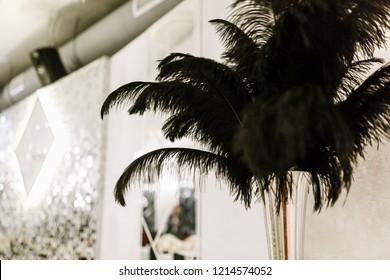 Black ostrich feather in black vase, wedding decoration details.