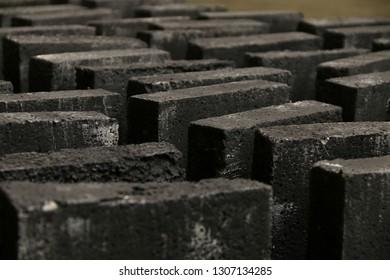 Black painted styrofoam bricks standing in rows