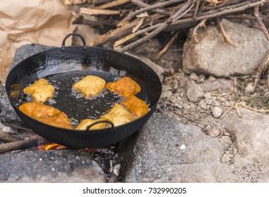 A black pan, resting on three large stones above an open fire is half filled with hot oil and Mandazi, East African donuts, that are almost cooked. Small sticks in a pile ready for stoking the fire.