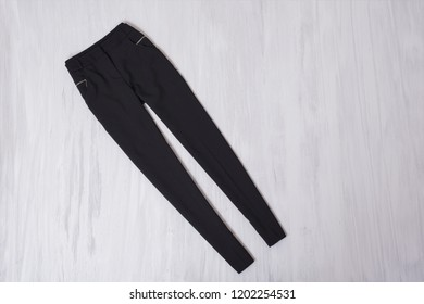 Black pants on wooden background. Fashionable concept