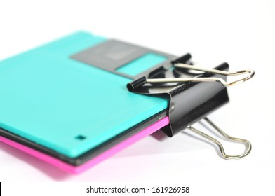 Black paper clip and floppy disk  isolated on white background.