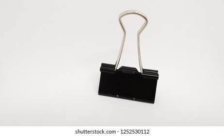 black paper clip with silver clamp isolated on white background studio closeup