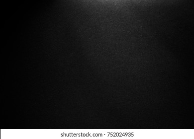 black paper texture or background with spotlight, dark wall backdrop wallpaper, dark tone.