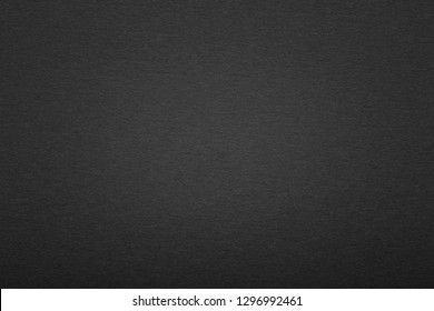 Black paper texture or background with vignette. Blank black page with vignette.