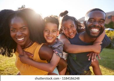 Black parents piggybacking their young kids, close up