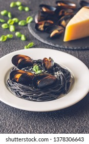 Black pasta with mussels and parmesan on the white plate