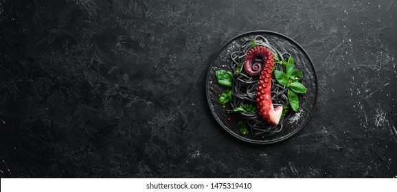 Black pasta with octopus tentacles. Seafood on a stone plate. In the old background. Top view. Free copy space.