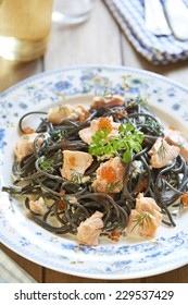 Black pasta with salmon and red caviar in cream sauce, italian cuisine