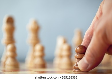 Black pawn on a chess board alone against all white pieces. Black pawn fights against white enemy team on board. Chess concept on blue background.