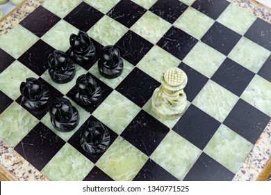 Black pawns pursuing the white king on the board