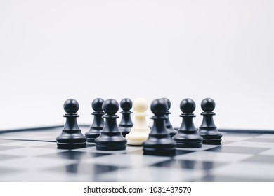 Black pawns siege white pawn, chess board game on white background, soft to focus, for ideas business leadership and teamwork concept.
