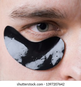 Black pearl extract. Skin care. Minimizes puffiness and reduce dark circles. Eye patches for men. Man with black eye patches close up. Metrosexual concept. Focused treatments for under eye area.