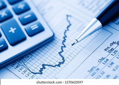 black pen and calculator on business graphs of stock and forex trends