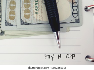 A black pen and cash dollars money on lined note sheet, with text written PAY IT OFF - concept of setting debt-free money goal  - first priority in financial management