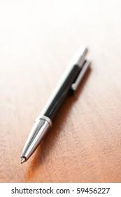 the black pen on wooden desk