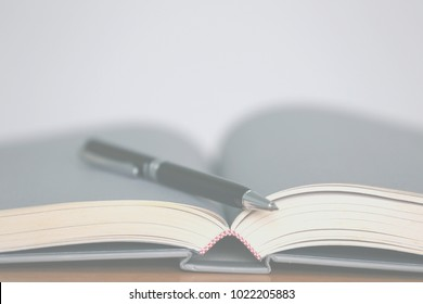 Black pen placed on open book selective focus and shallow depth of field