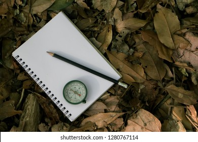 Black pencil with notebook and Compass on leaves background