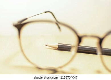 Black pencil is on the brown notbook in frame of blurred glasses.