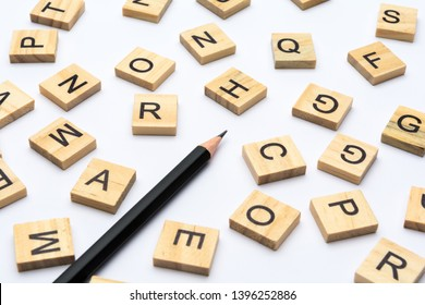 Black pencil and scattered alphabet letters on wooden blocks on white background