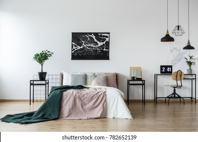Black pendant lamps above simple desk near cozy king-size bed in open floor plan interior with minimalist design and wooden details