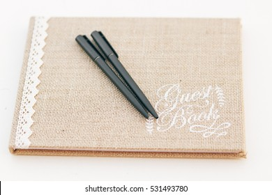 Black pens lie on flaxen Guest Book