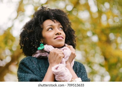 Black pensive woman wearing warm scarf looking up to the autumn trees at the park.