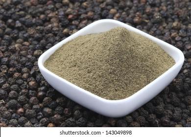 Black Pepper corns and Black Pepper Powder on square bowl. Focus on Black Pepper Powder in full-frame.