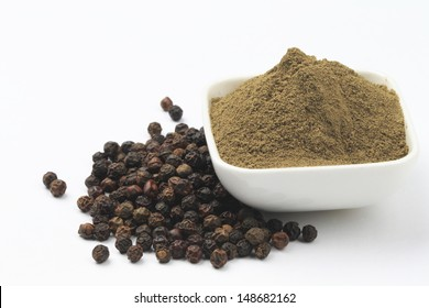 Black pepper corns scattered on white background and Black pepper Powder on white bowl isolated on white background.