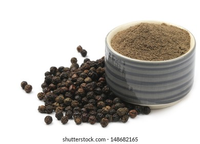 Black pepper corns scattered on white background and Black pepper Powder on bowl isolated on white background.