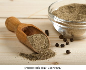 black pepper powder on wooden spoon
