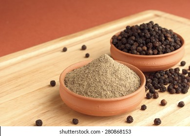 Black pepper powder and black pepper in terracotta pots on wooden plank