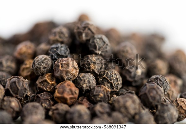 Black pepper seeds on a white background with some blurry effects (bokeh) applied. Organic seeds origin from Sarawak of Borneo, Malaysia.