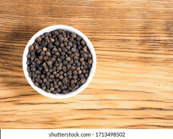 Black pepper in white bowl on brown wood background with copy space. Healthy eating, ayurveda, naturopathy concept