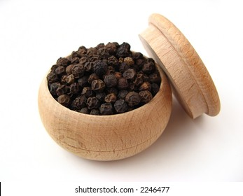 Black pepper in wooden pot over white.