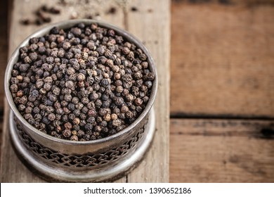 Black peppercorns in bowl on wooden background